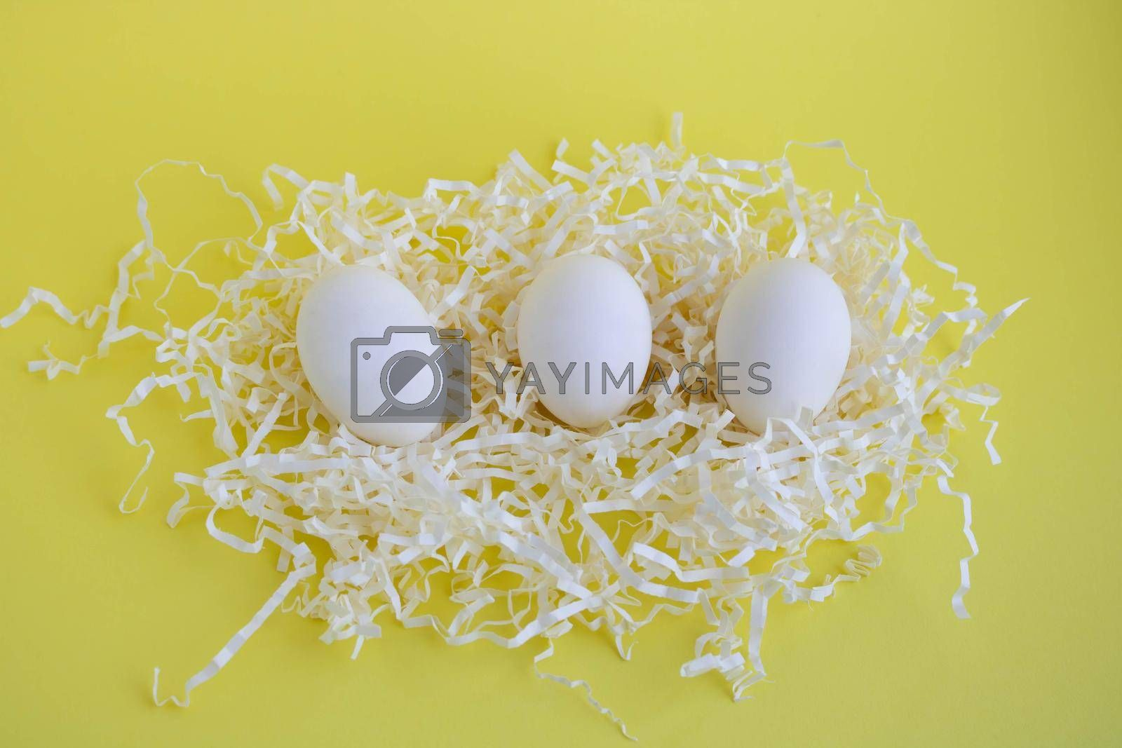 Three white eggs in tinsel on a yellow background. Easter Concept.