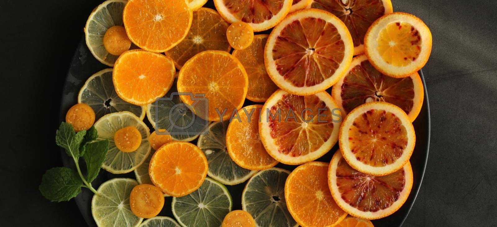 Fresh citruses on round plate on dark black stone background, flat lay. Oranges, clementine, mandarins, limes. Top view. Dramatic kitchen