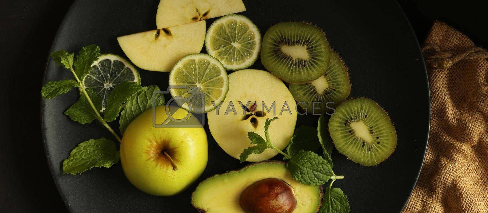 citrus fruits on black background with canvas, top view. Dramatic kitchen with green fruits