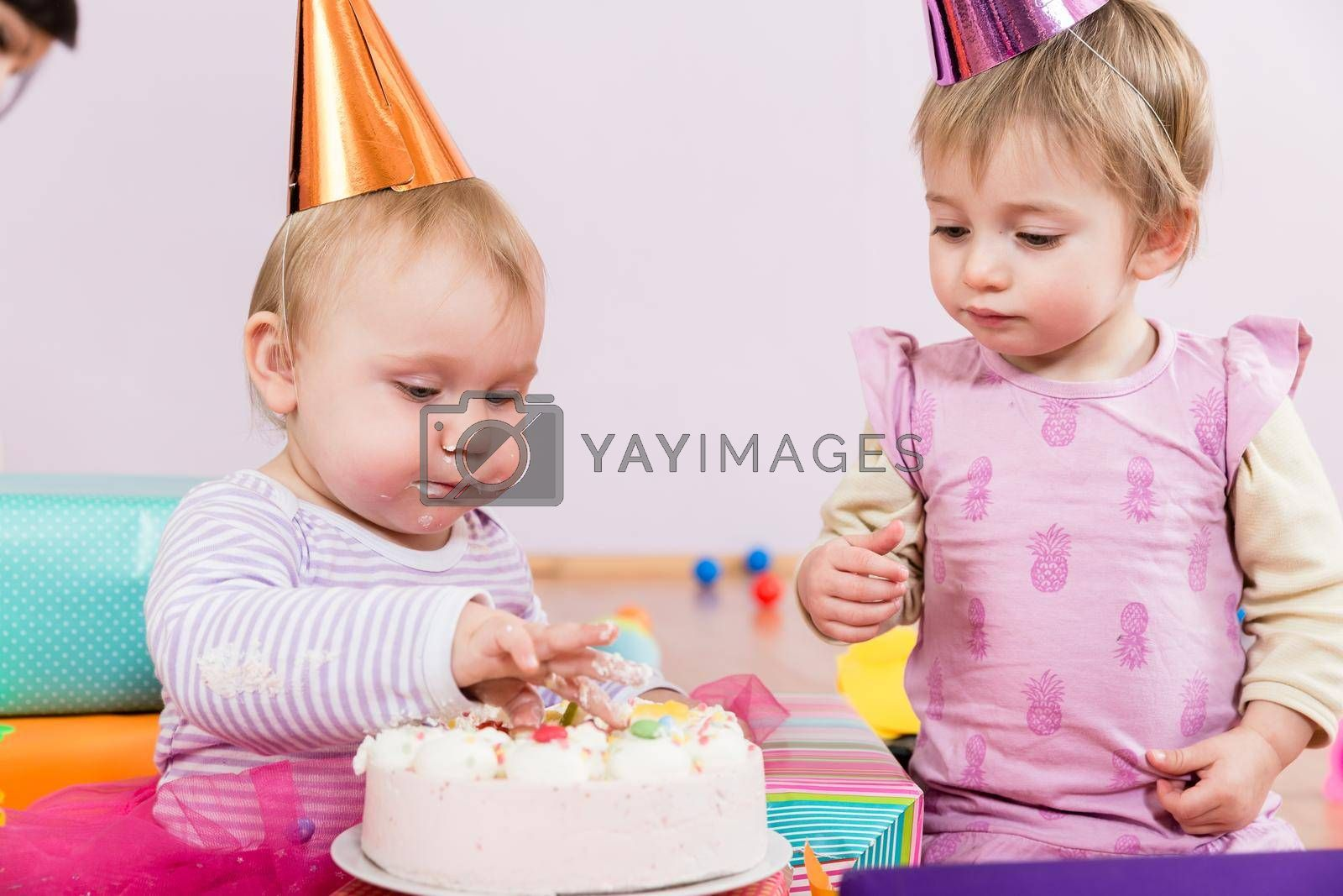 Royalty free image of Two toddlers with birthday cake by Kzenon