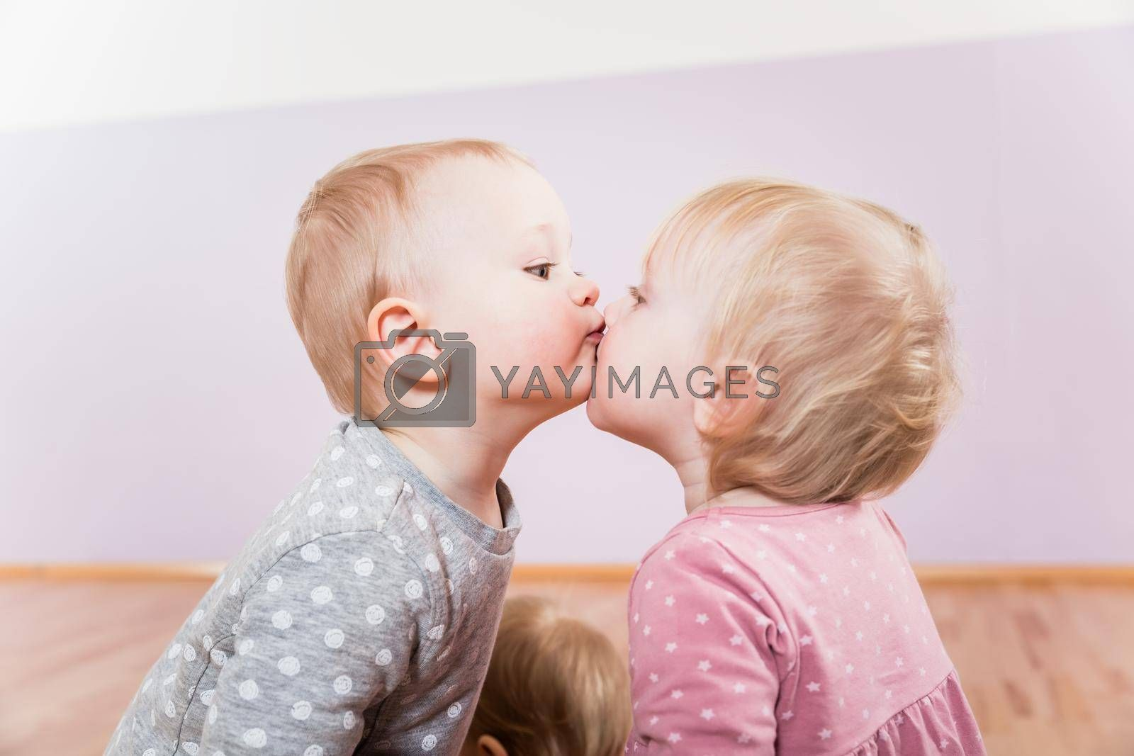 Royalty free image of Two toddlers playing with each other by Kzenon