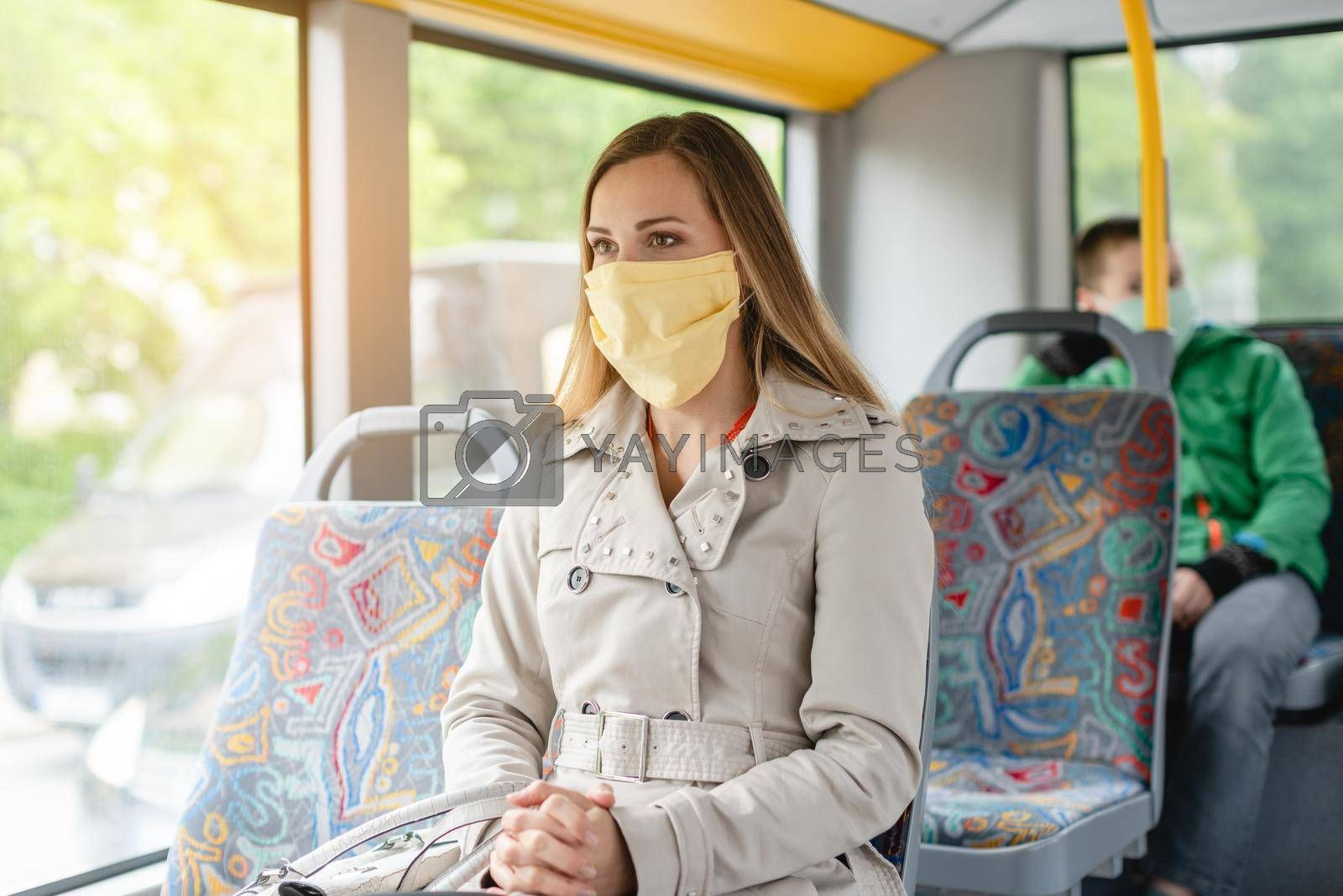 Royalty free image of Woman using public transport during covid-19 crisis by Kzenon
