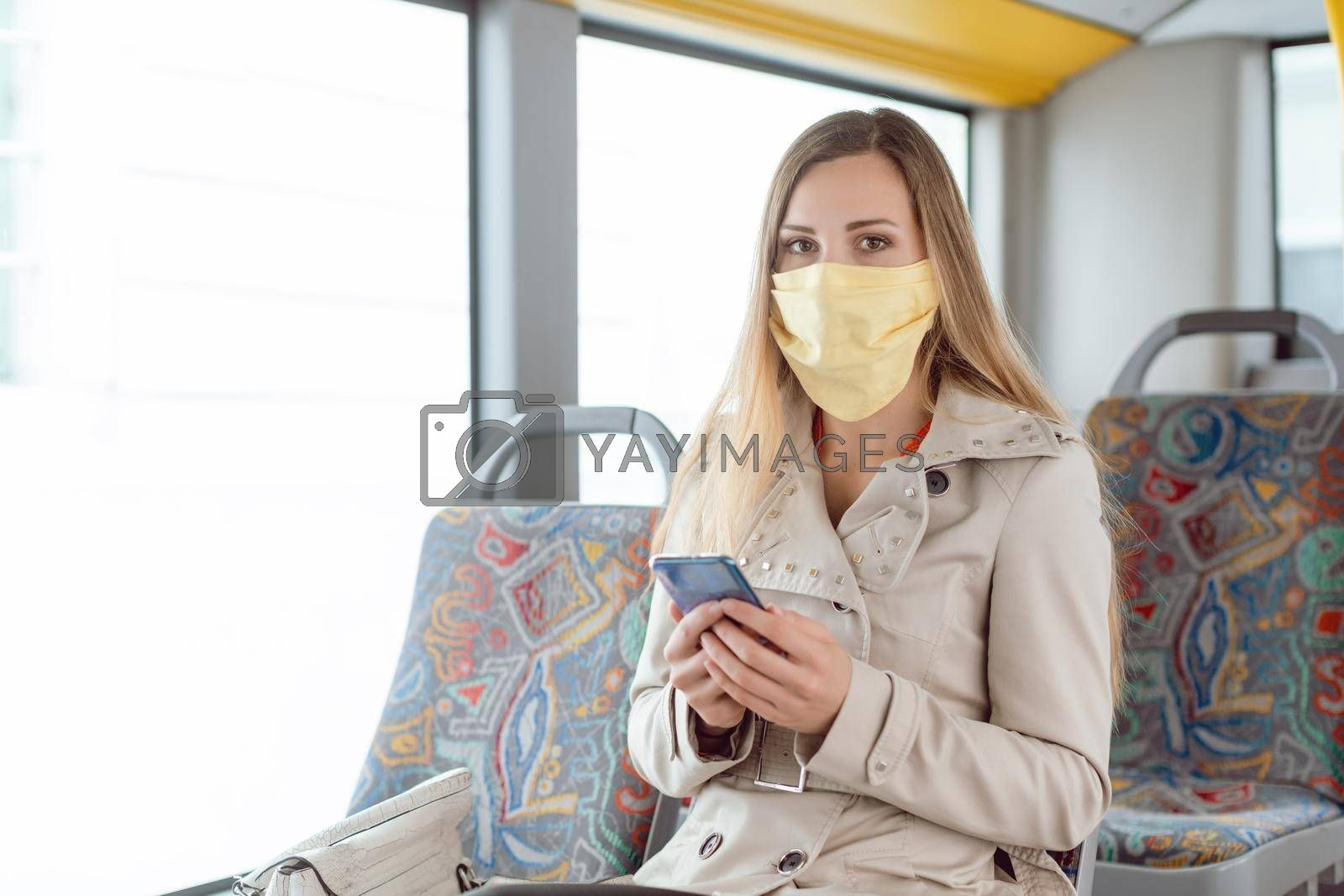 Royalty free image of Woman using phone in the bus wearing a face mask by Kzenon