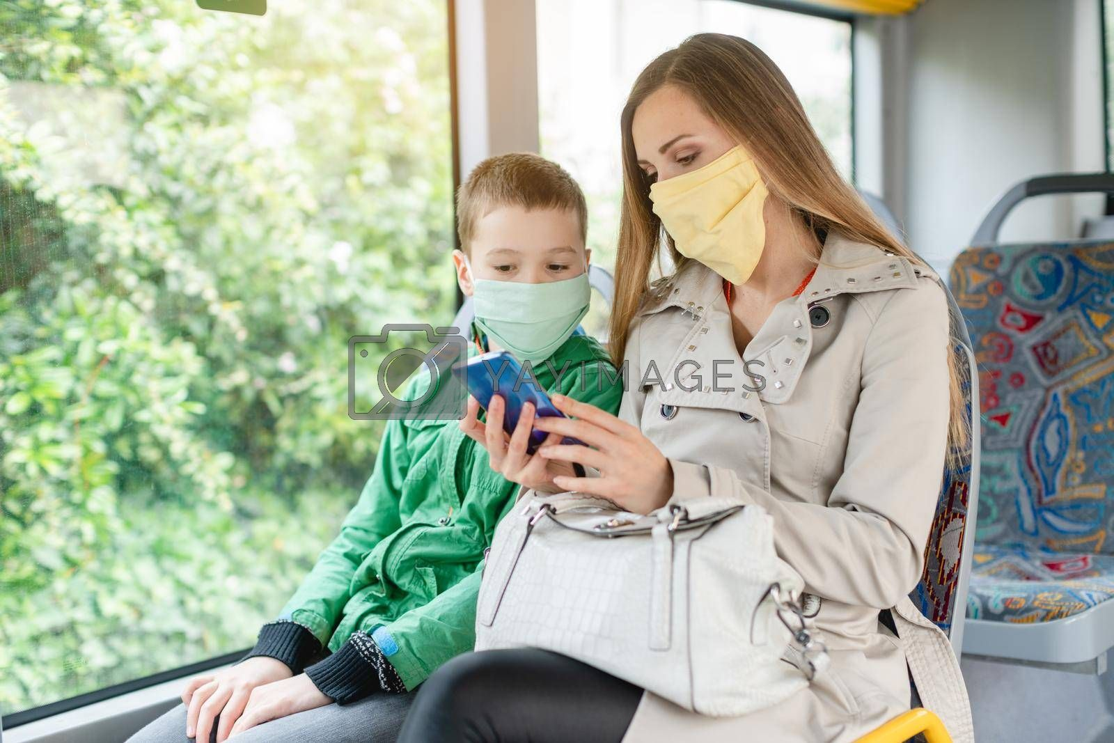 Woman with her son in the bus during coronavirus crisis looking at the phone