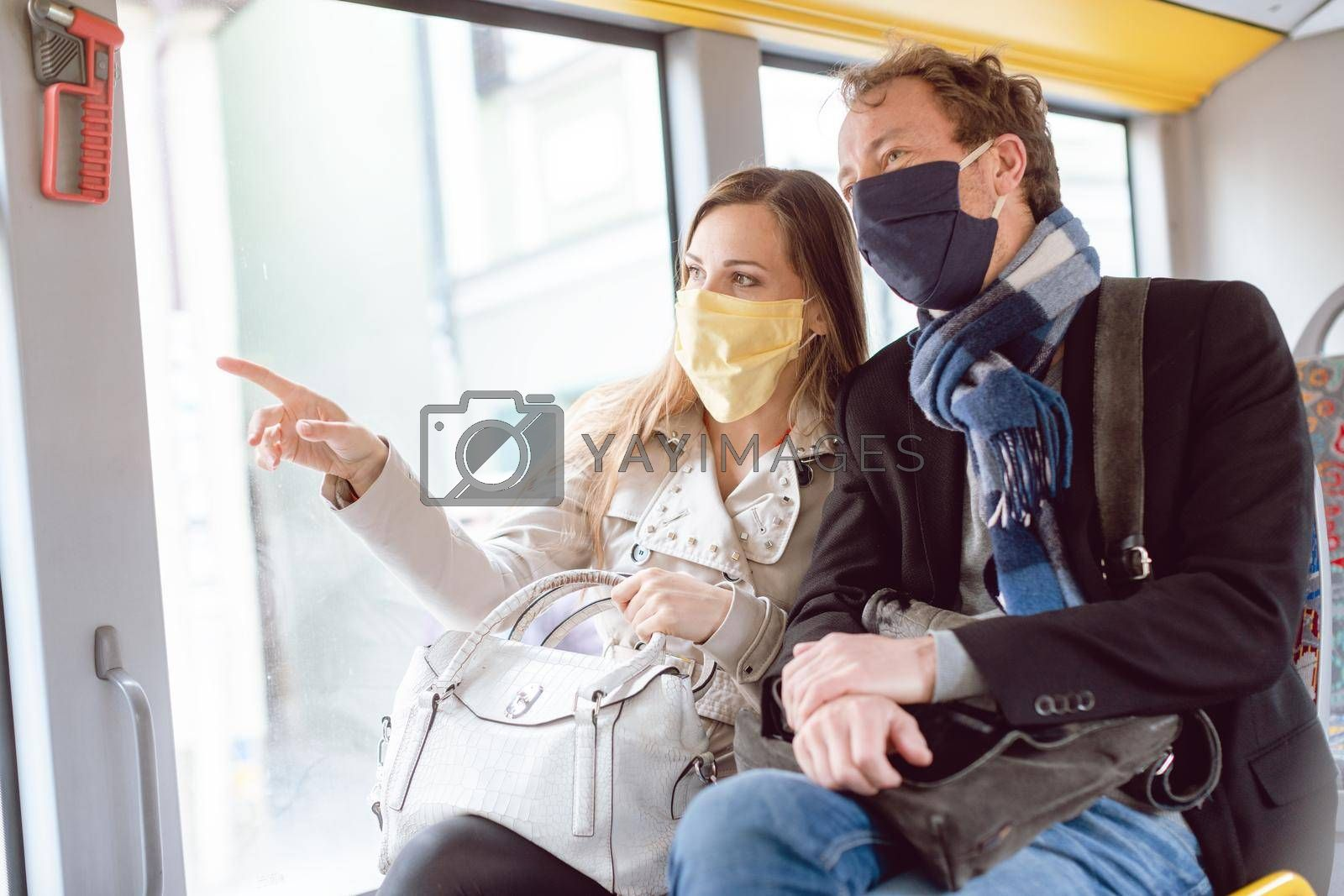 Couple in public transport bus wearing masks due to virus pandemic