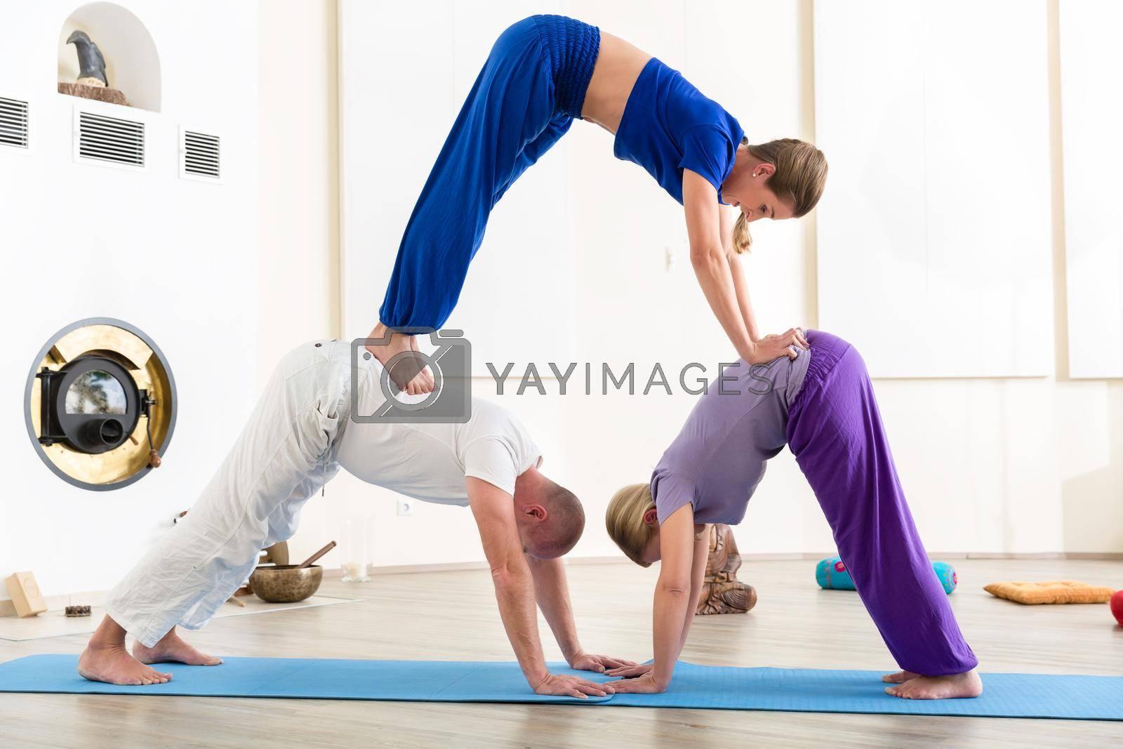 Group of people making pyramid yoga pose