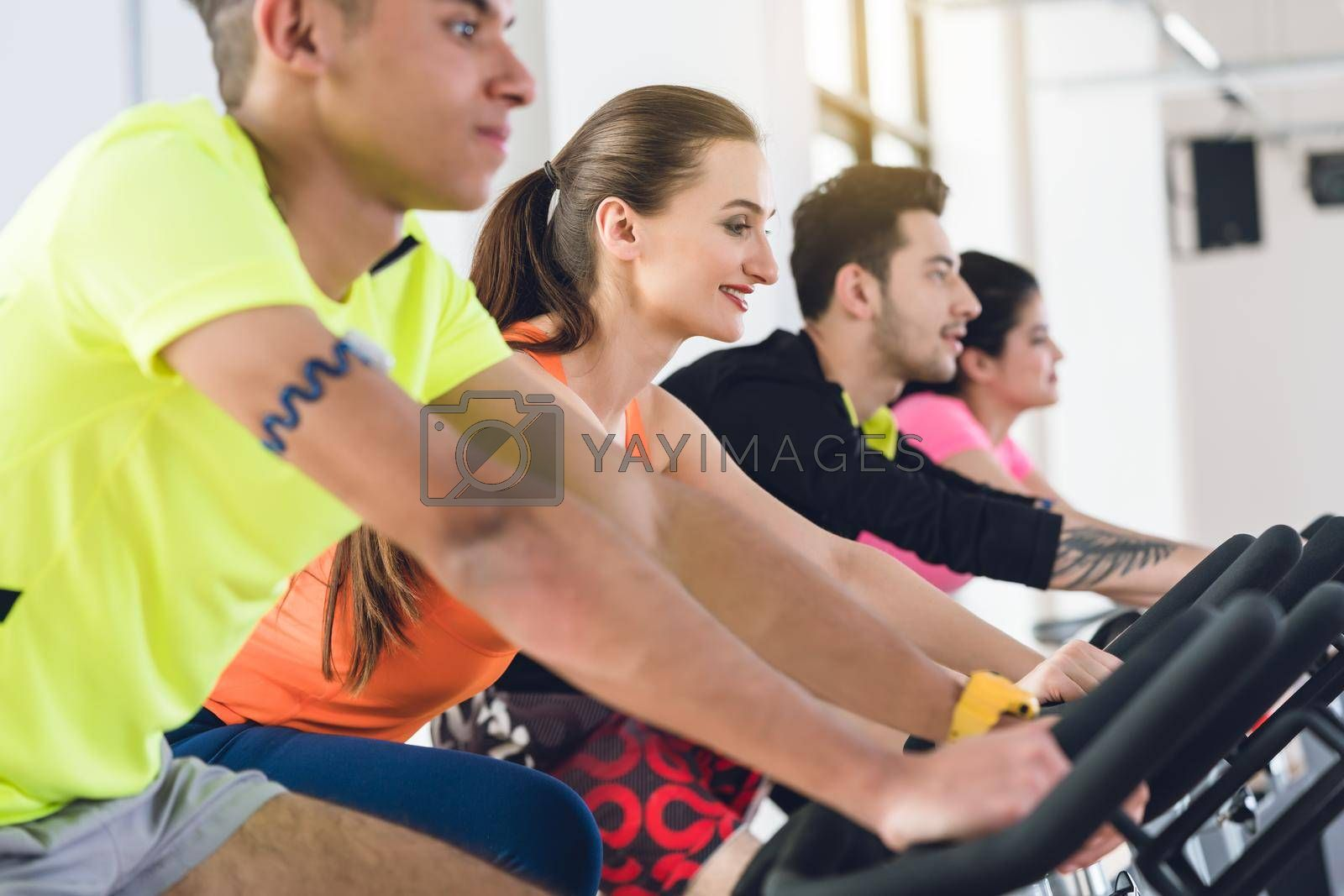 Group friends cycling in a row at gym