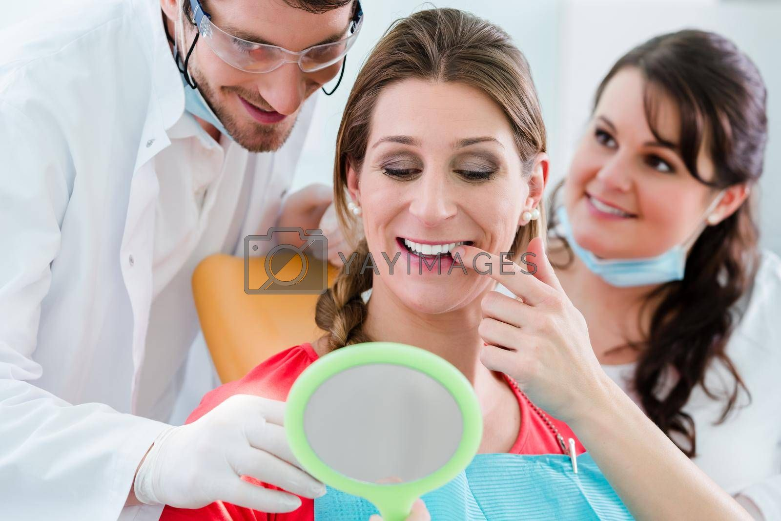 Royalty free image of Woman after dental bleaching at dentist by Kzenon