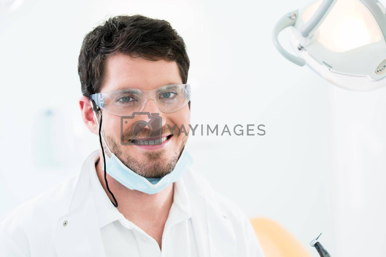 Royalty free image of Dentist standing in dental surgery by Kzenon