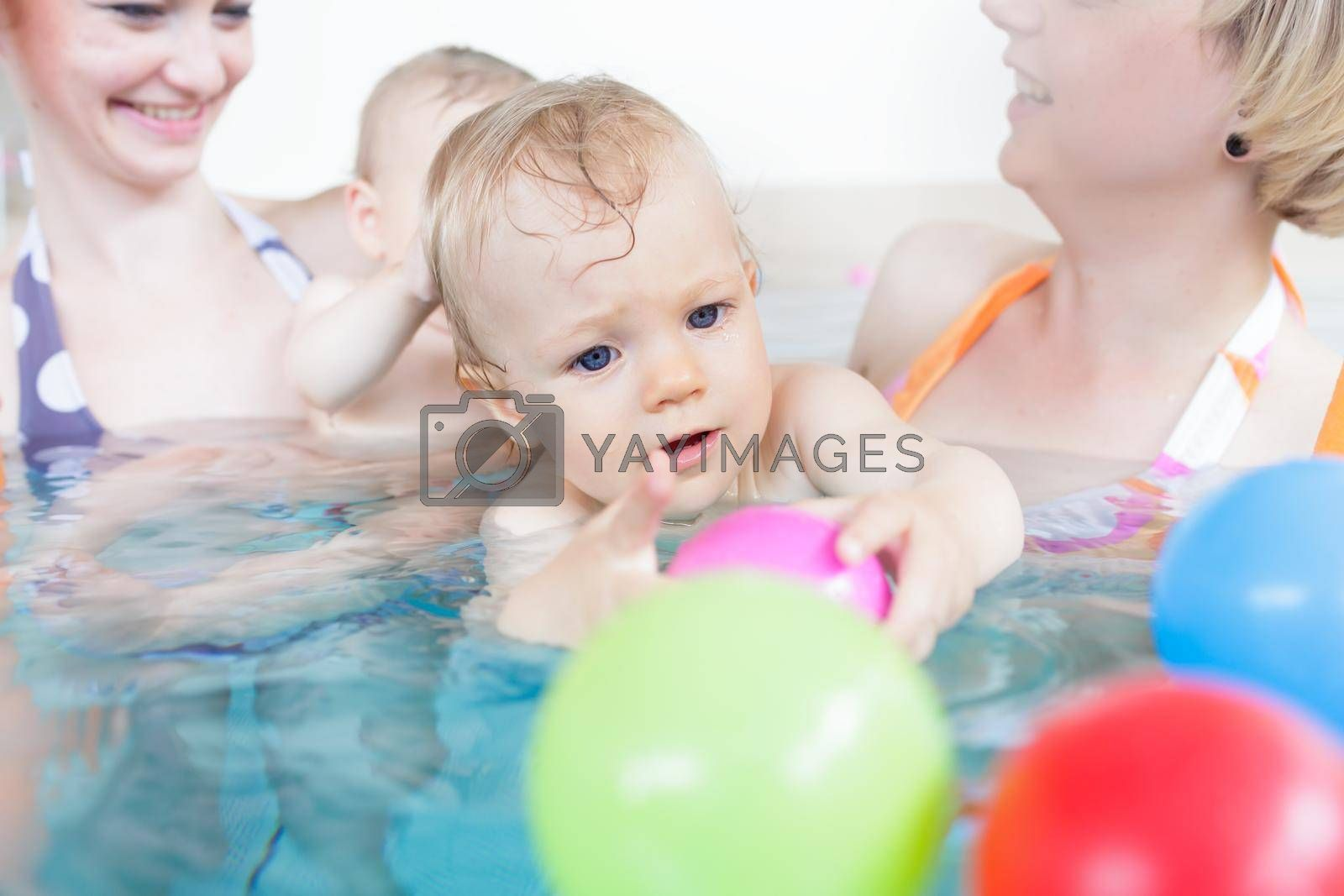 Royalty free image of Mothers being happy about their babies playing with each other by Kzenon