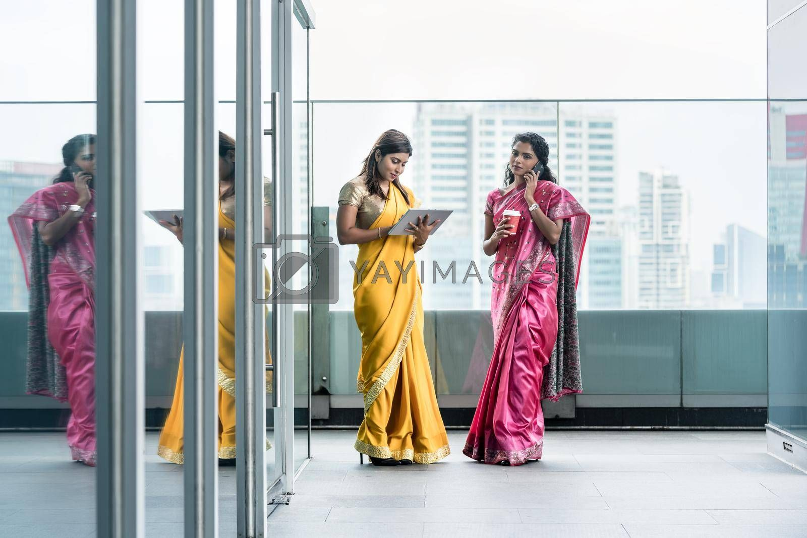 Two young Indian women using modern technology for communication during the break at work in a business building