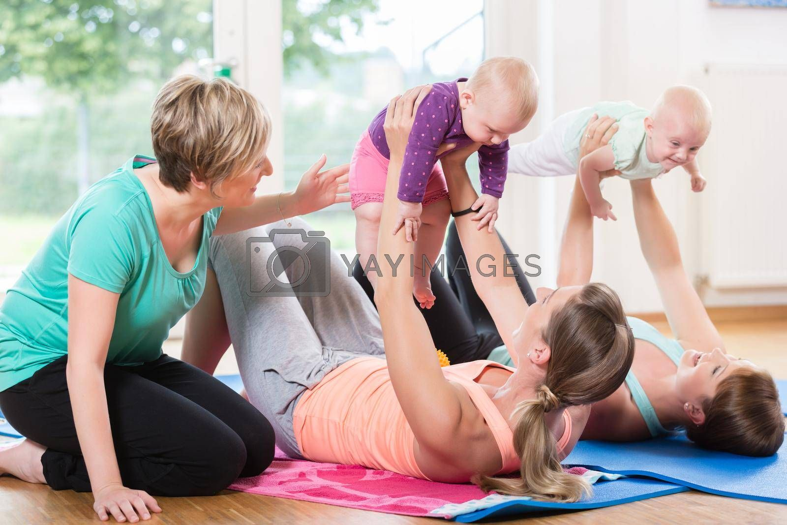 Royalty free image of Women and their babies in mother-child gymnastic course by Kzenon