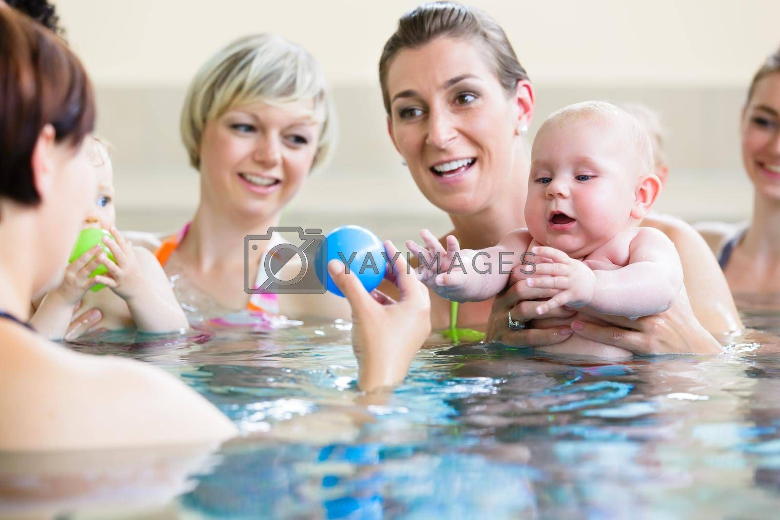Royalty free image of Babies and their moms at mother-and-child-swimming class by Kzenon