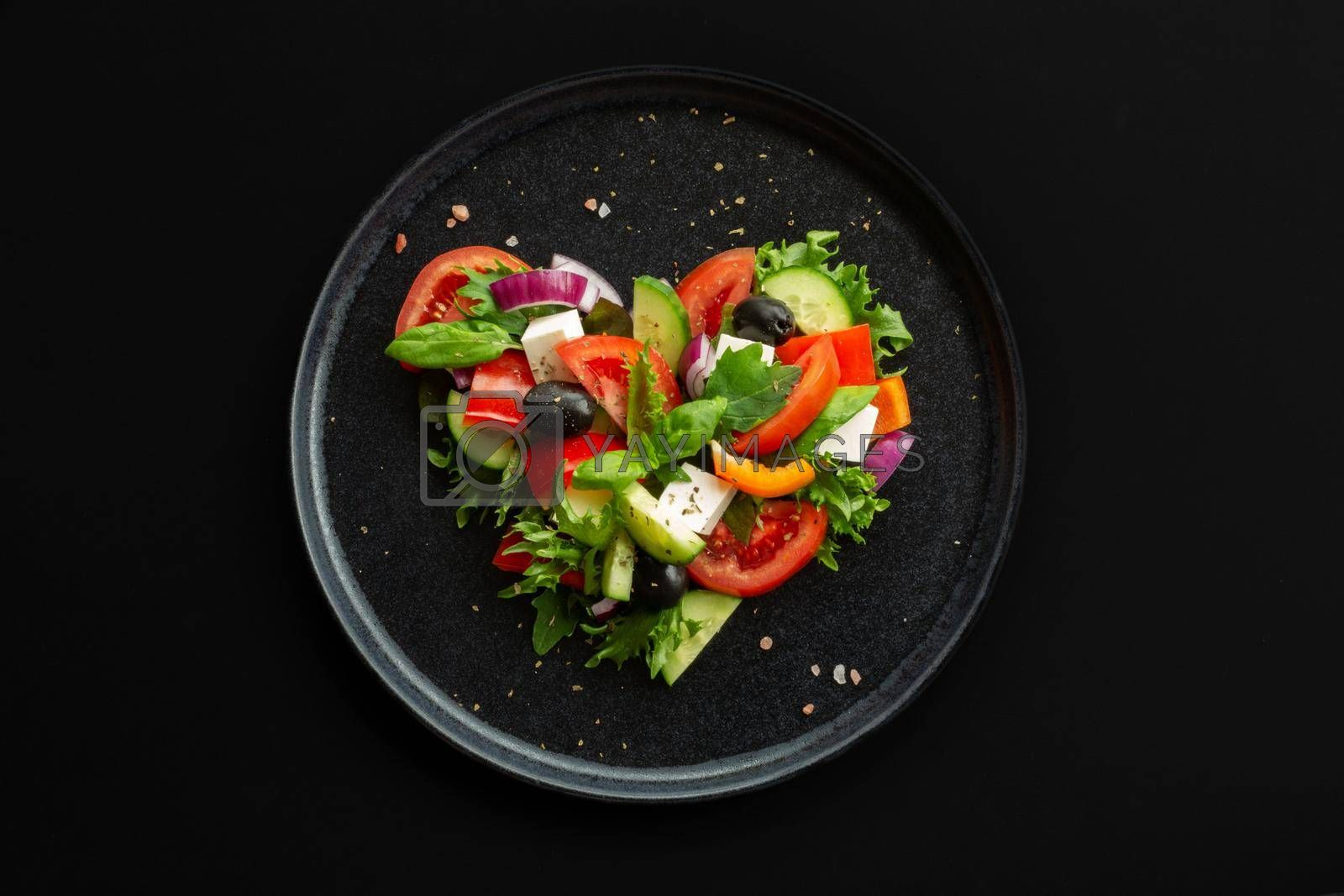 Greek salad in heart shape love food concept, black stone luxury plate, top view flat lay design, black background