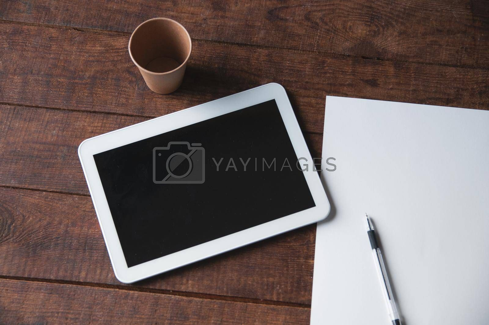 Modern office workplace with tablet pc on the table. On the table there is a tablet and a white sheet of paper with a pen. For a design presentation or portfolio.