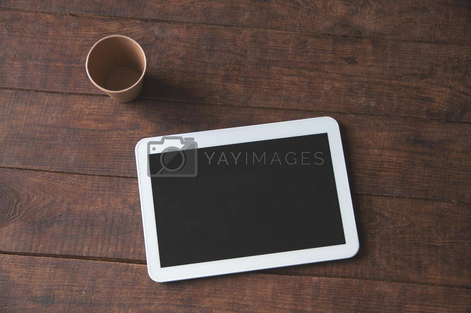 Modern office workspace with tablet pc on the table and a disposable cup of coffee. For a design presentation or portfolio.