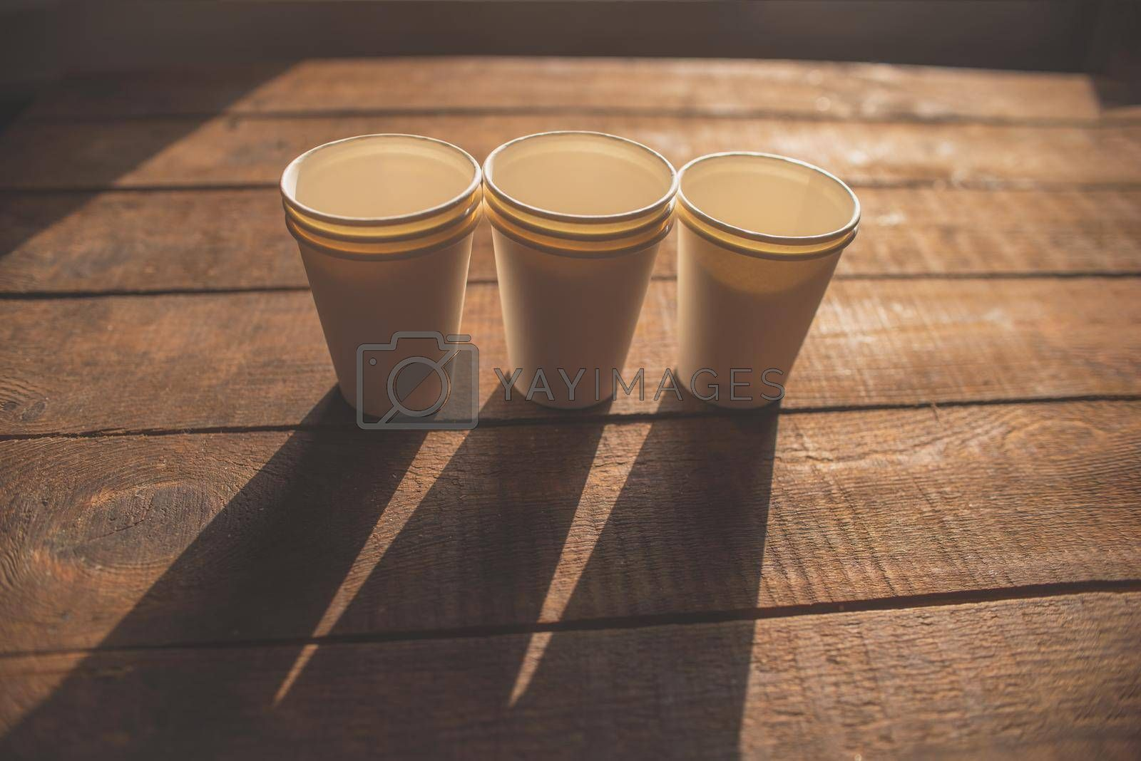 disposable white cardboard cups stand on a wooden table on a brown background