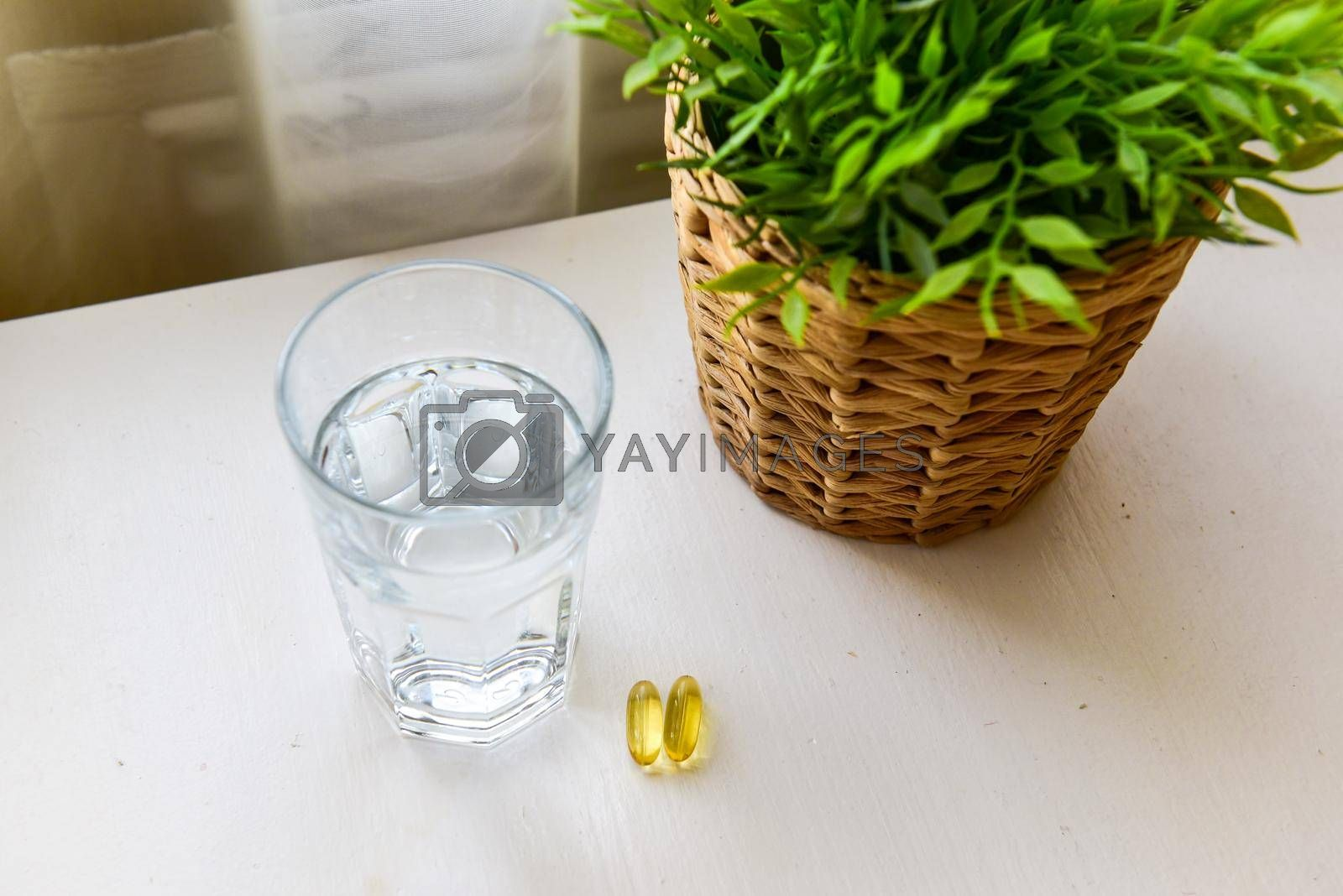Omega-3, spirulina, chlorophyll capsules and glass of water on white wooden table. Dietary supplements, biologically active additives. vitamin pills. Health support.