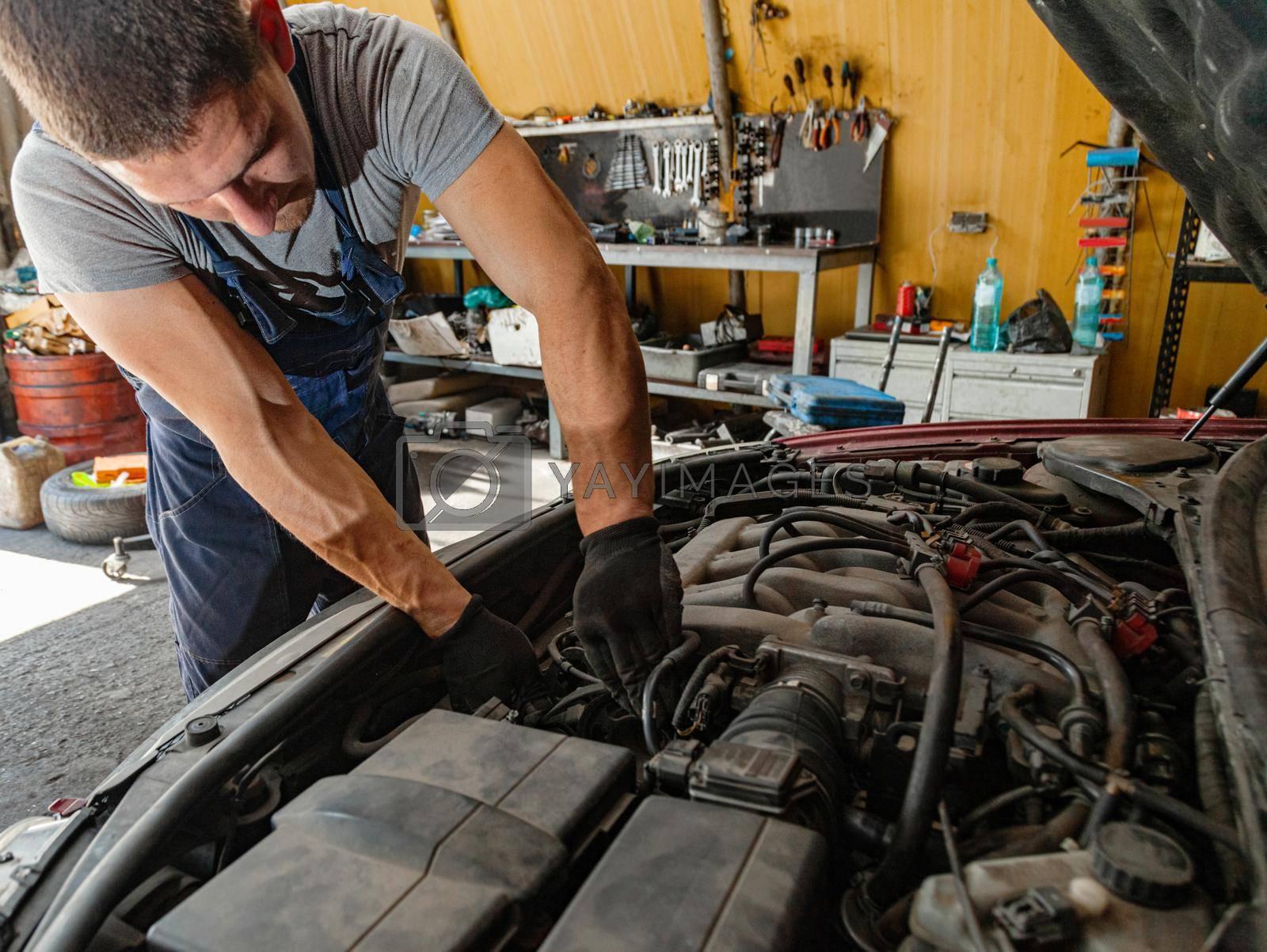 Royalty free image of Car Engine Repair Technician Mechanic Shop Worker by vilevi
