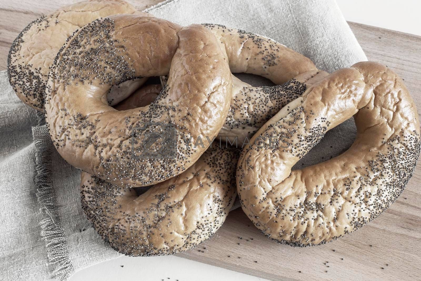 Royalty free image of Bagels with poppy seeds on a cutting board by georgina198
