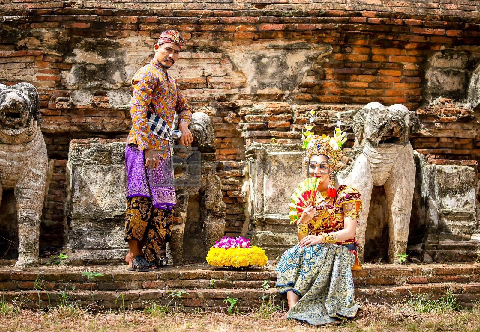 Portrait Of Smiling Young Woman In Balinese Traditional Clothing Holding Flower Bouquet At Temple