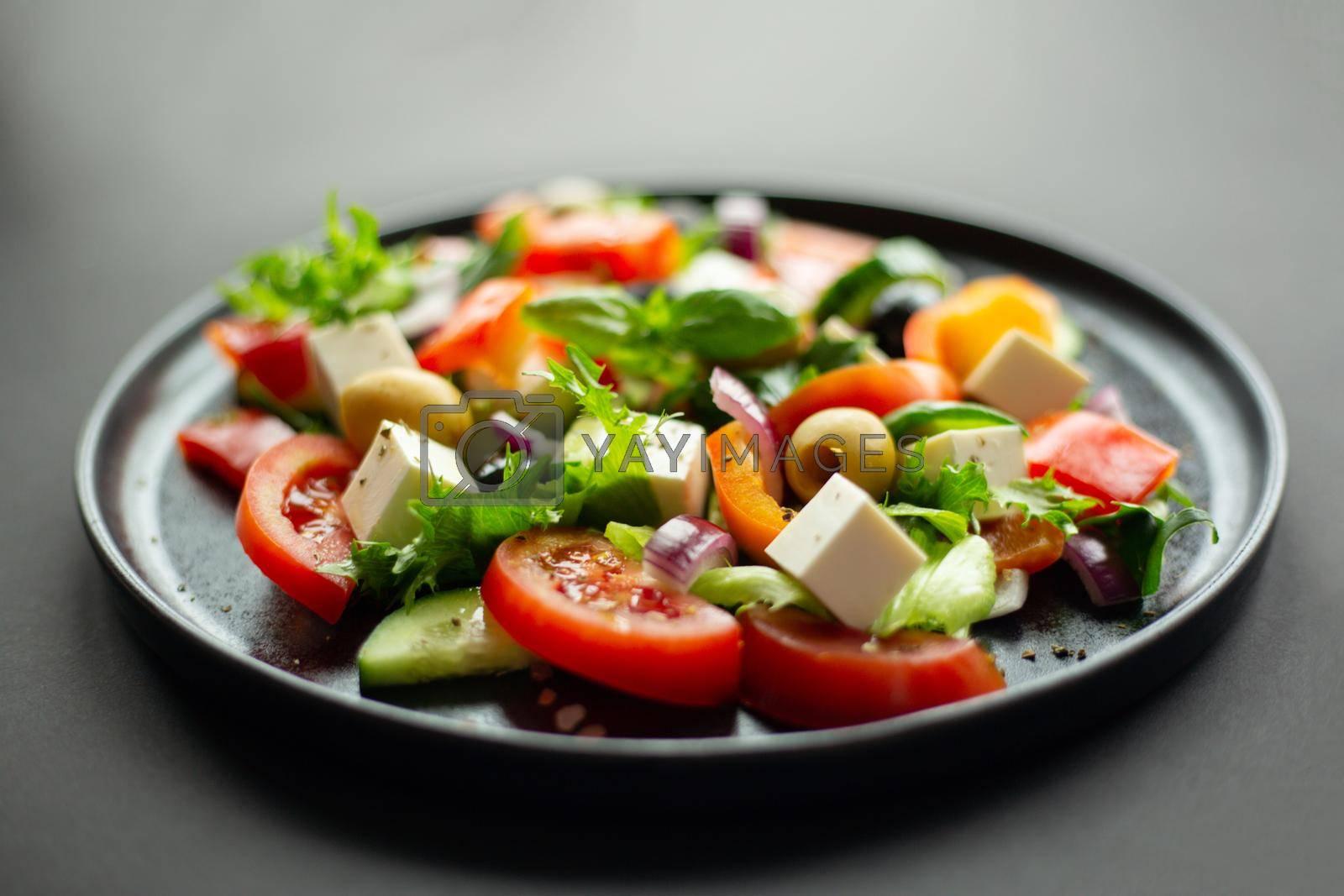 Greek salad side view on black table over black table background