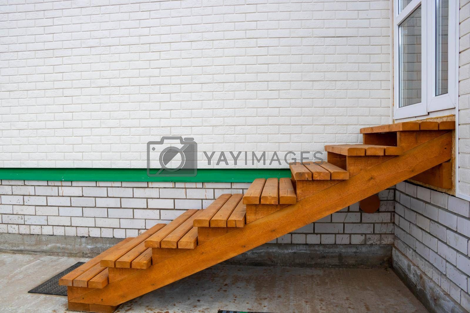 Wooden staircase painted with stain, entrance to the house.