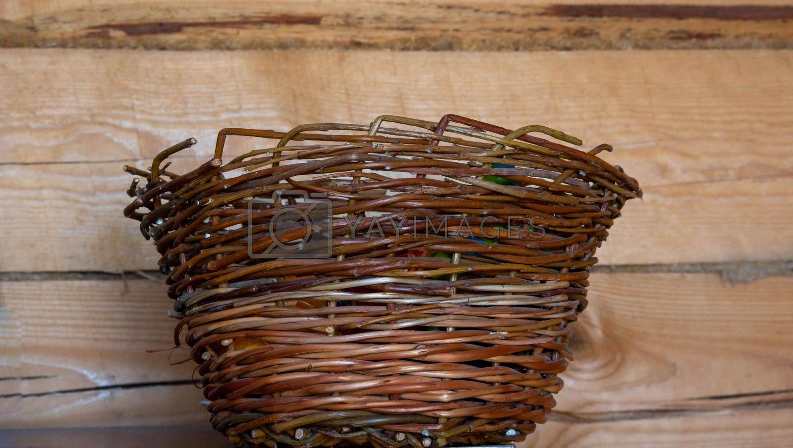 An empty wicker willow basket on a wooden background.