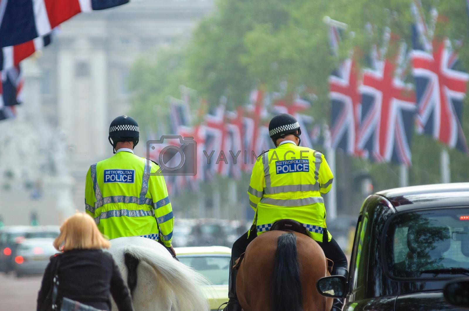 LONDON, UK - CIRCA APRIl 2011: Two mounted police officers on the Mall, Buckingham Palace in the background.