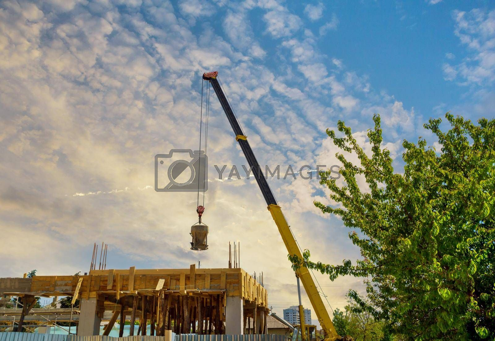 Tanks for transportation of concrete mix on a building site with bucket liquid concrete container with hanging on crane hook