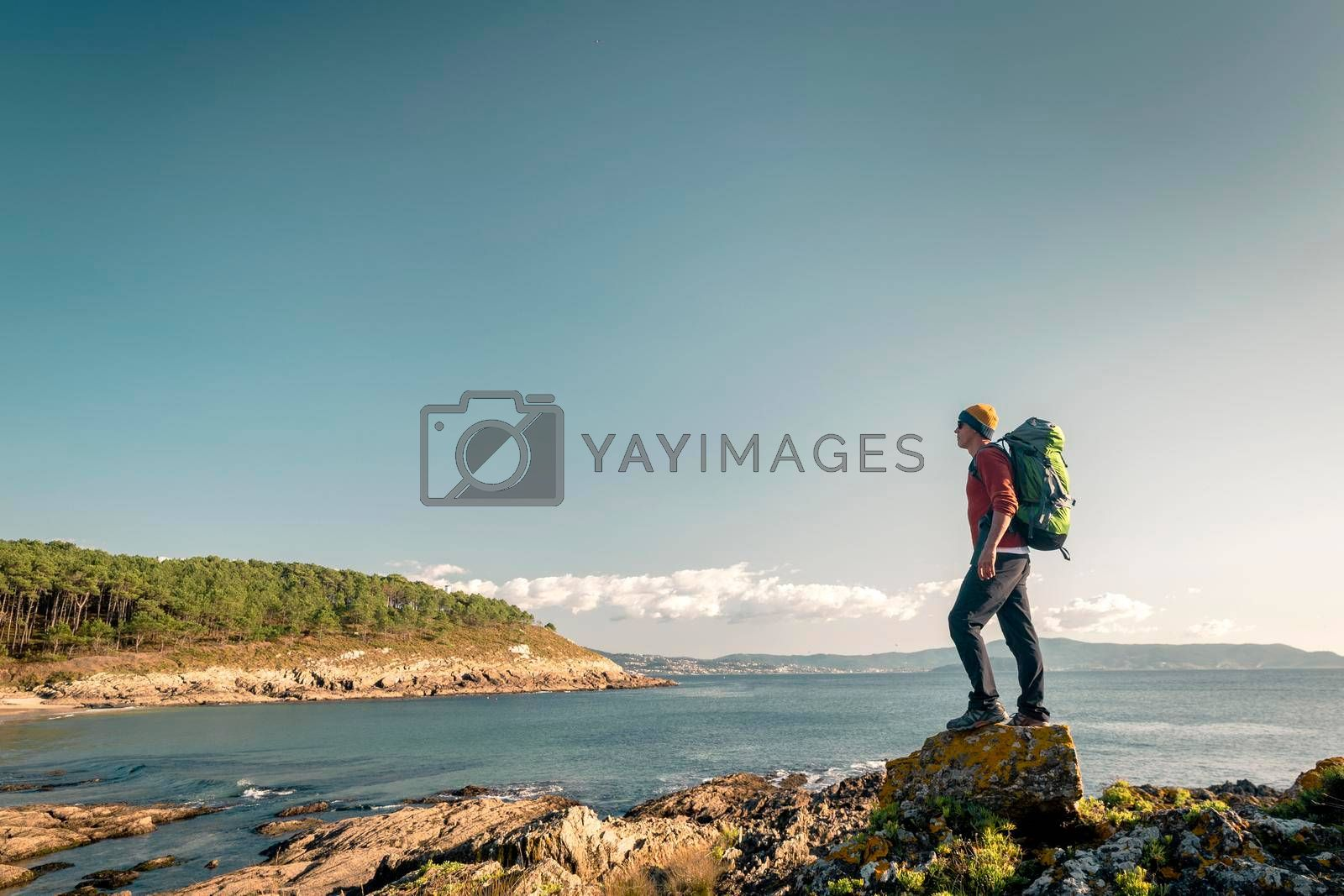 Royalty free image of Man exploring the coastline with backpack by Iko