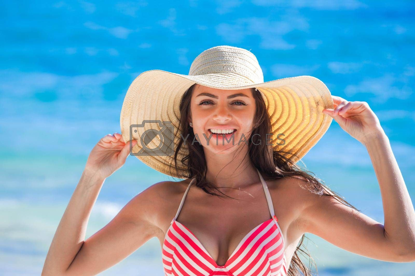 Royalty free image of Woman wearing sunhat on beach by Yellowj
