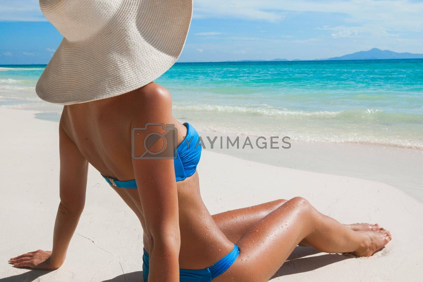 Royalty free image of Woman in sun hat sitting on beach by Yellowj
