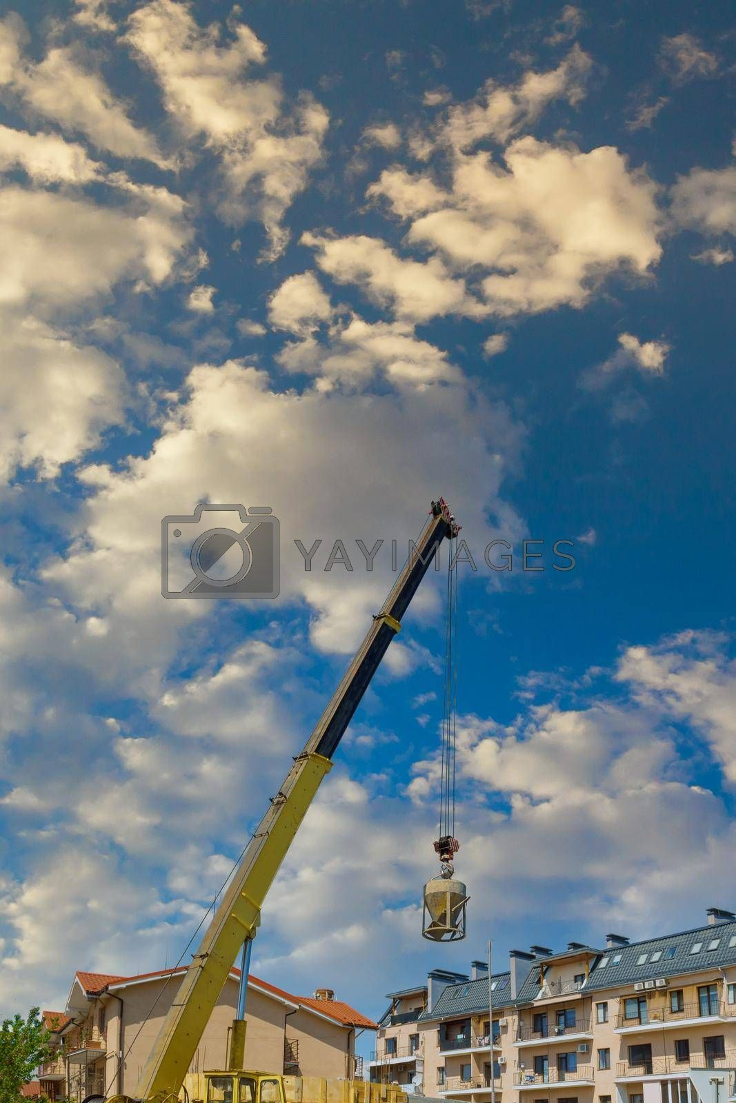 Heavy construction machinery with cement concrete bucket hanging with wire rope crane