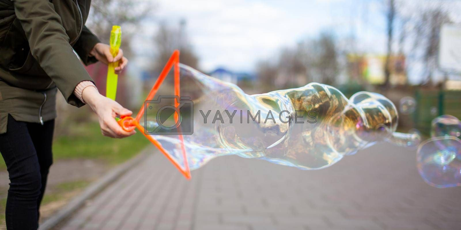 A girl blows soap bubbles in the park for the entertainment of children. Large, colorful soap bubbles in the open air in a public park.