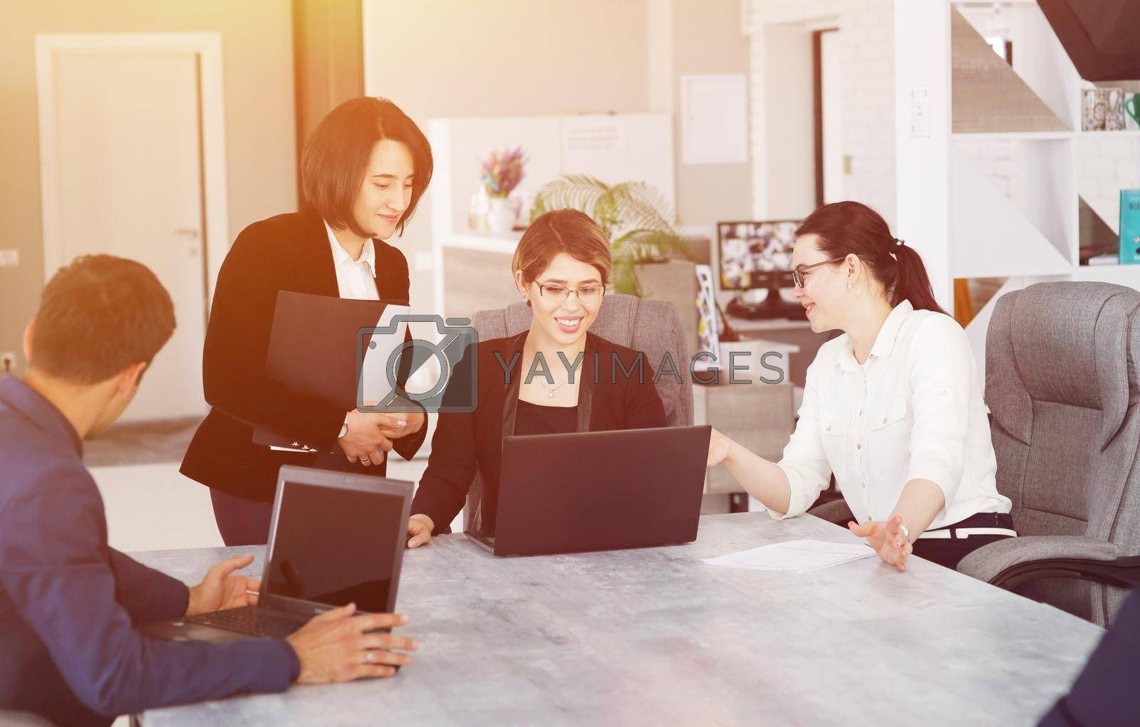Royalty free image of Three young successful business women in the office working together on a project by selinsmo