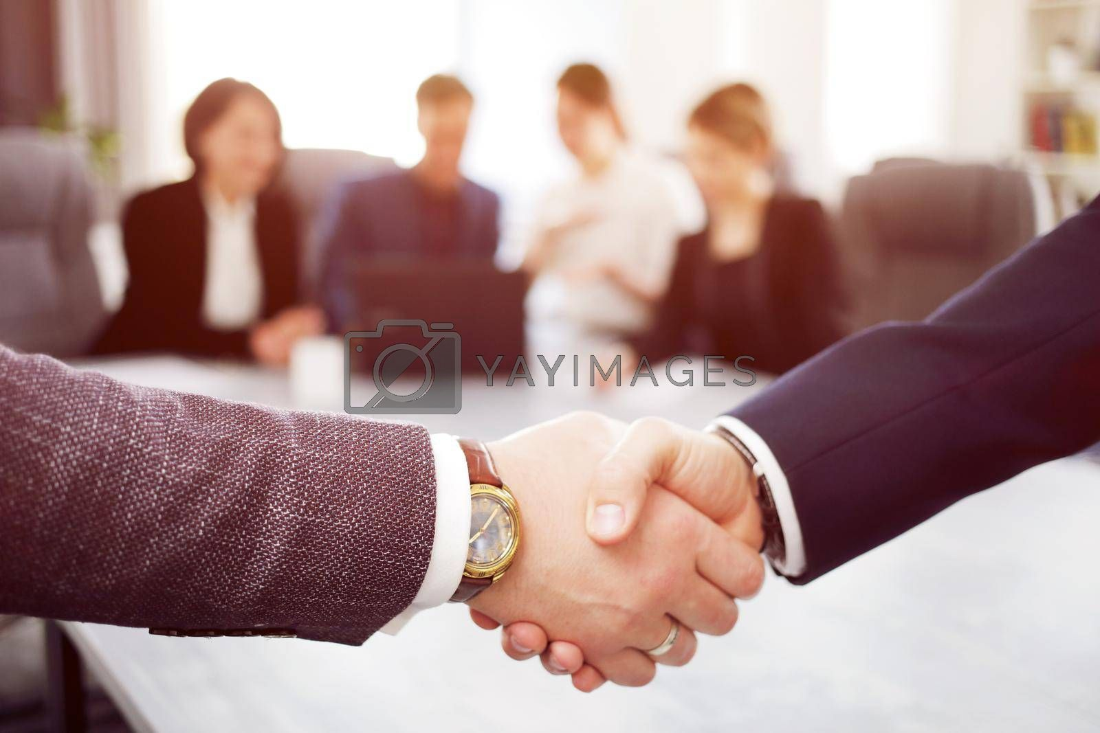 Royalty free image of Business people shaking hands finishing a meeting in the background of their work team by selinsmo