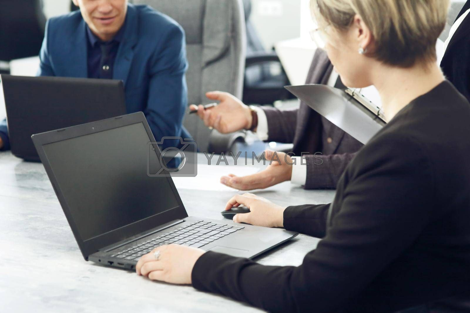 Royalty free image of Laptop against the background of a group of young business people in the office discussing a work idea together by selinsmo