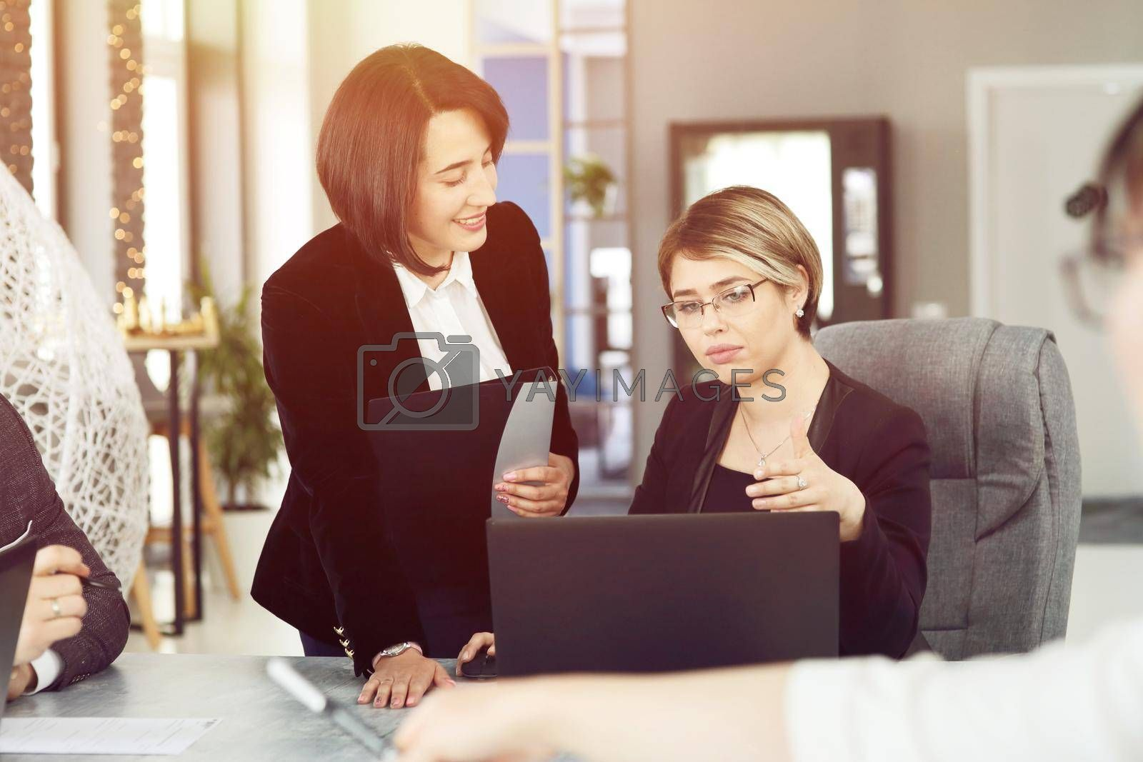 Royalty free image of Two young business women in the office, analyzing information looking into a laptop and smiling by selinsmo