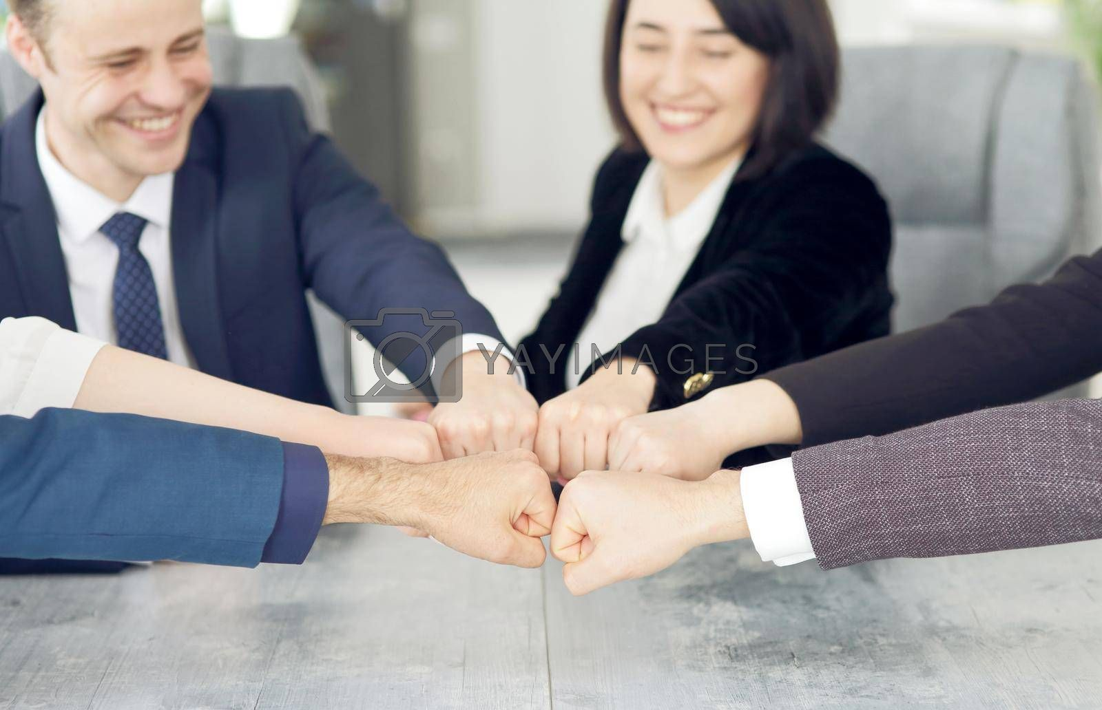 Royalty free image of Unity and teamwork concept of young business people folding their hands together by selinsmo