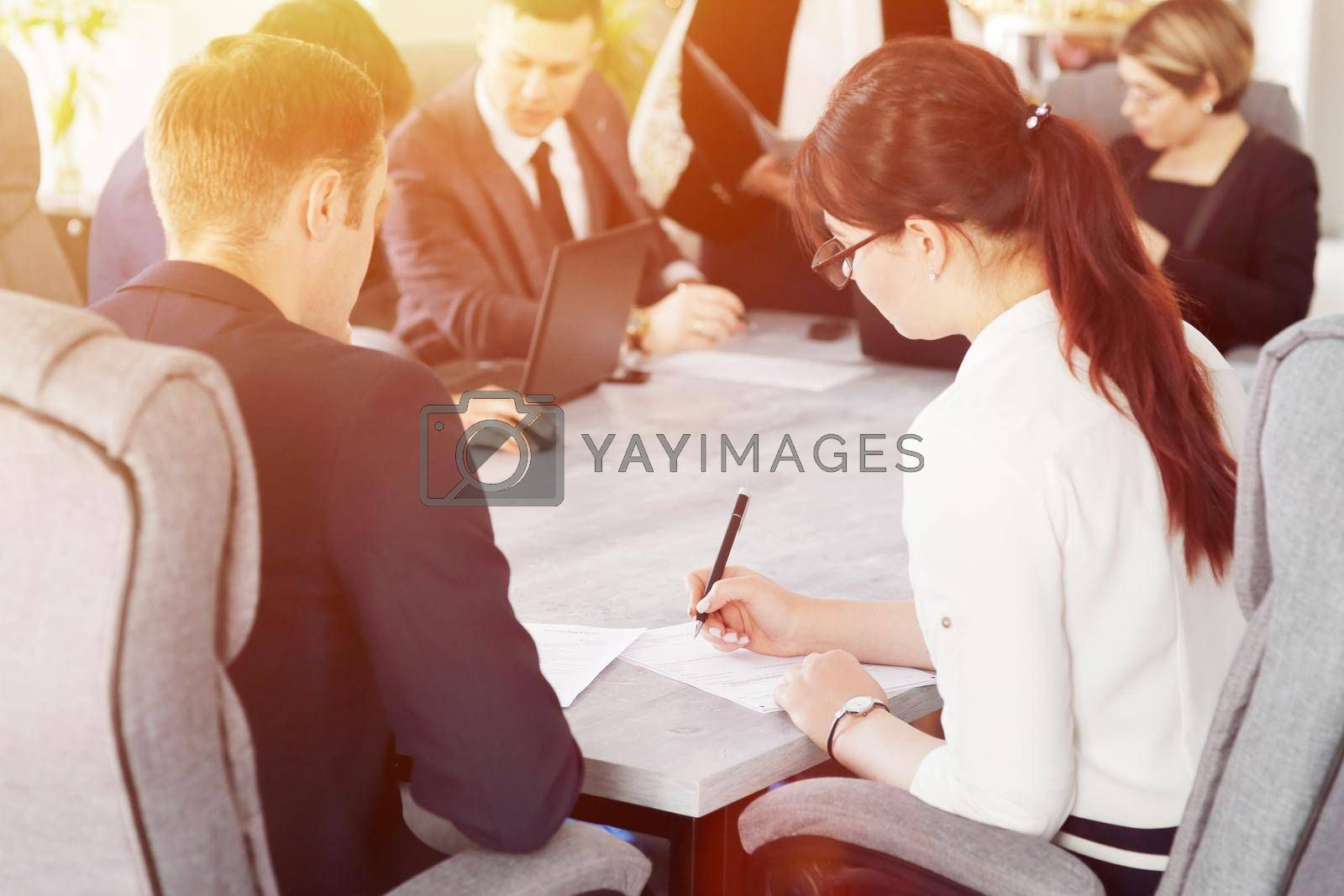 Royalty free image of Group of young successful businessmen lawyers communicating together in a conference room while working on a project by selinsmo