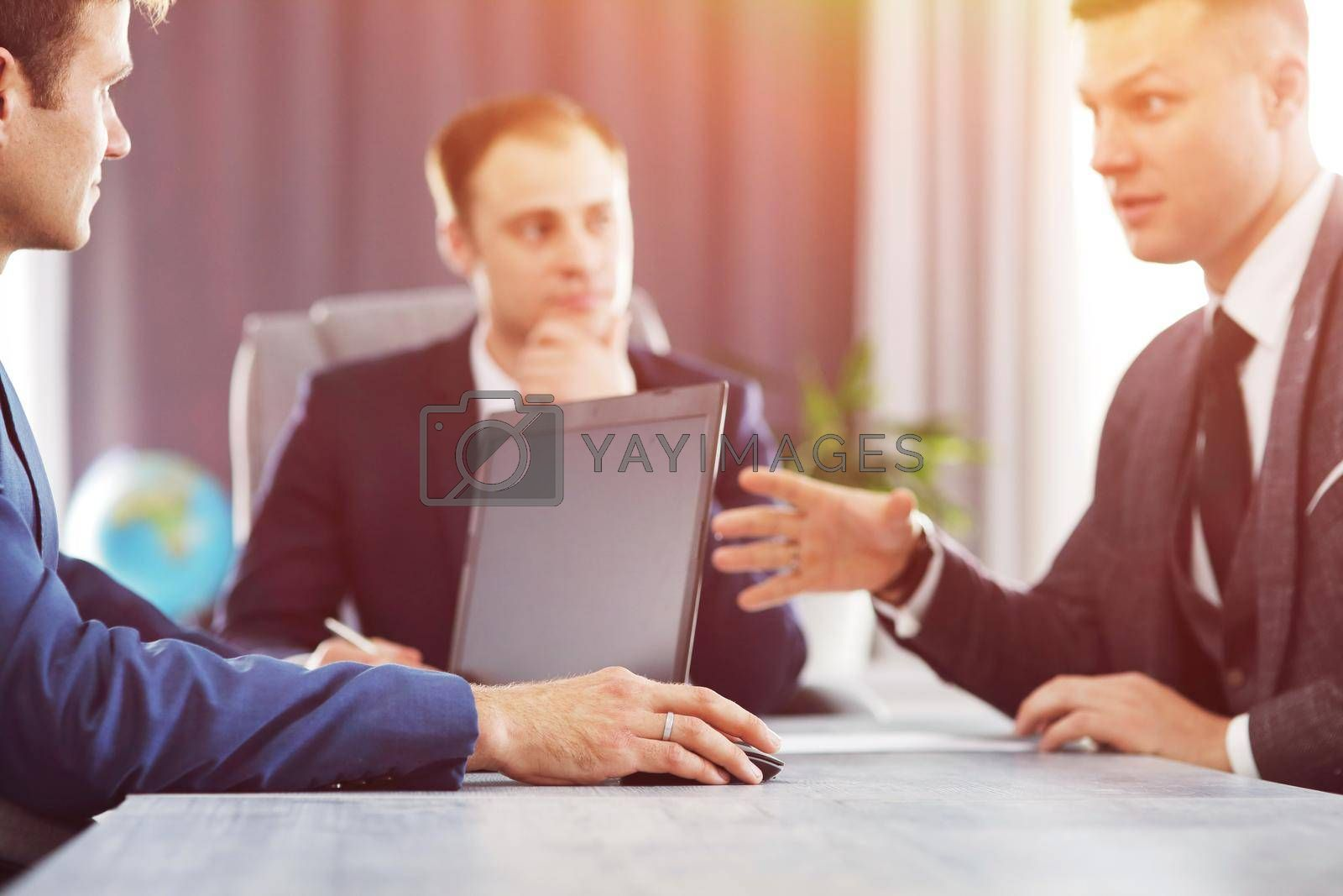 Royalty free image of Three of young business man meeting in the office discussing an important idea together by selinsmo