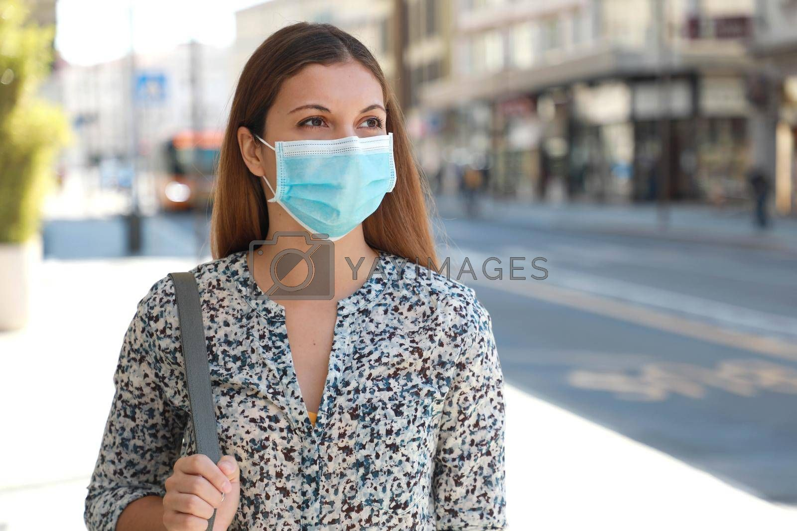 Young business woman with surgical mask waiting bus on bus stop in city street
