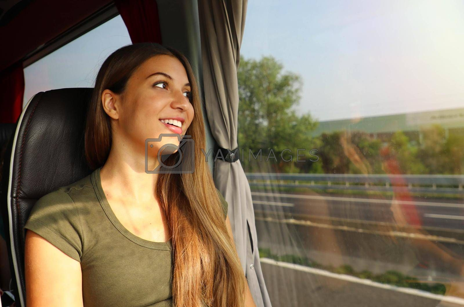 Young beautiful woman looking through the bus window. Happy bus passenger traveling sitting in a seat and looking through the window.