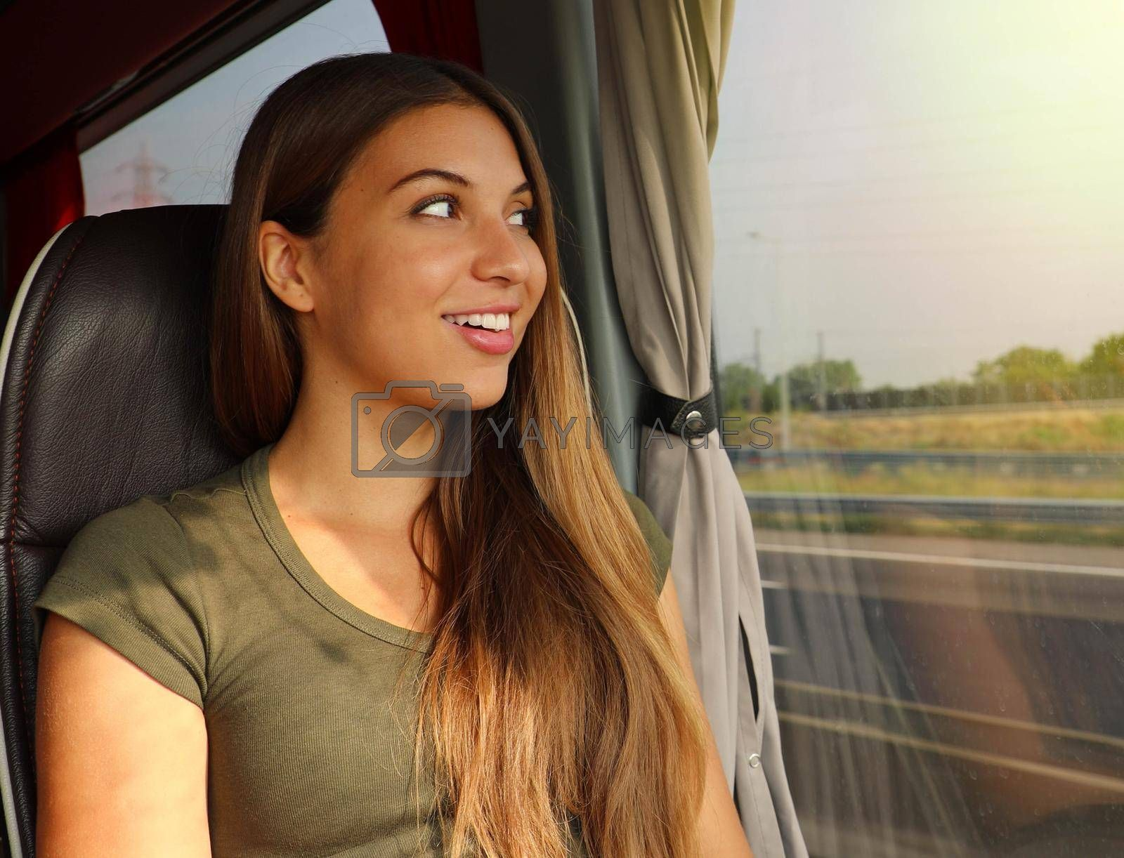 Easy travels. Traveller girl using comfortable bus to move. Young beautiful woman looking through the bus window. Happy bus passenger traveling sitting in a seat and looking through the window.