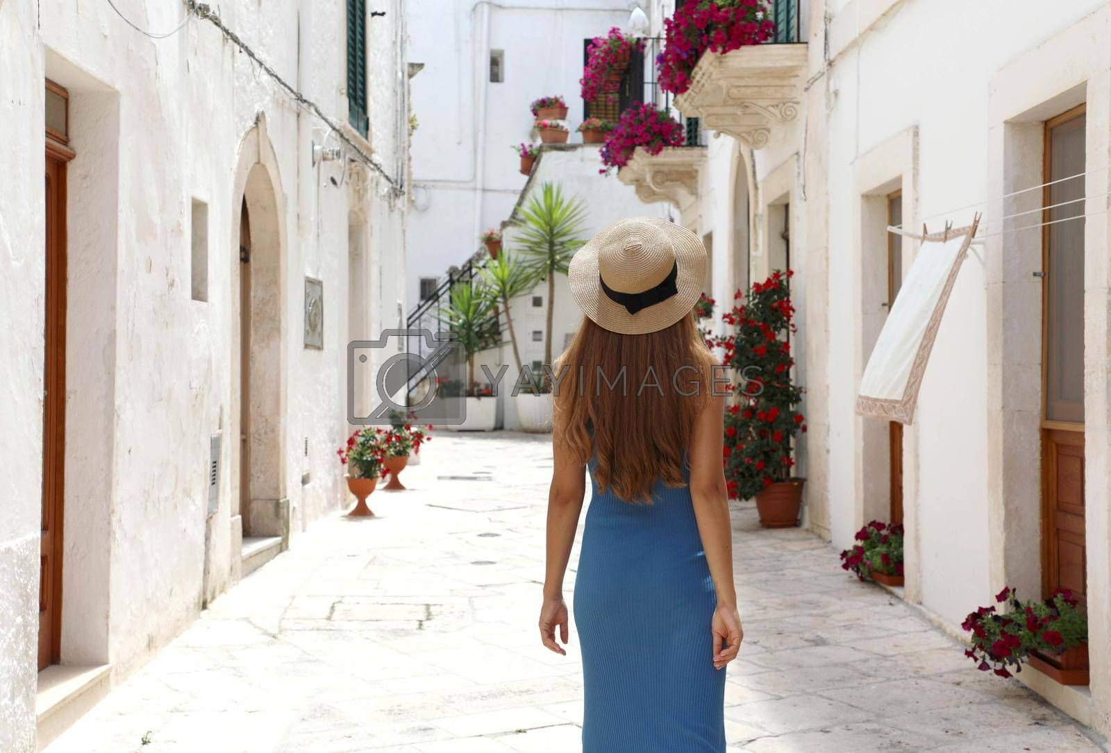 Back view of female tourist walking in old town. Travel woman in straw hat and blue dress enjoying vacation in Europe. Tourism and travel concept.
