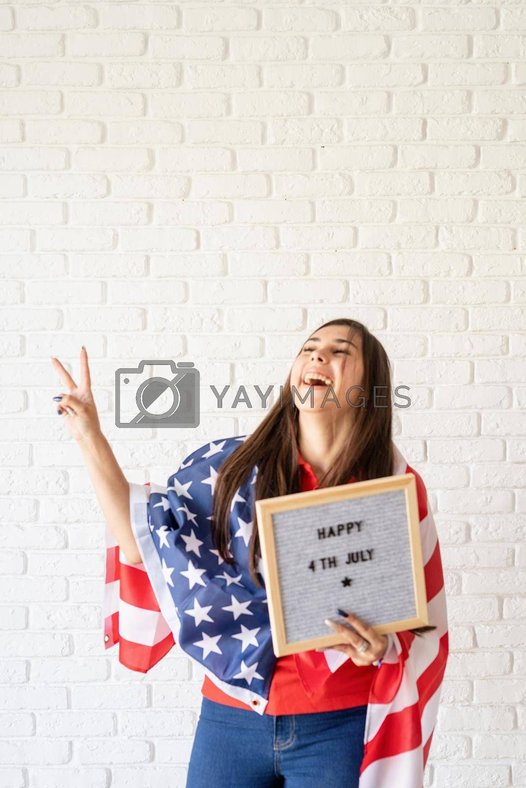 Independence day of the USA. Happy July 4th. Woman with american flag holding letter board with words Happy 4th July