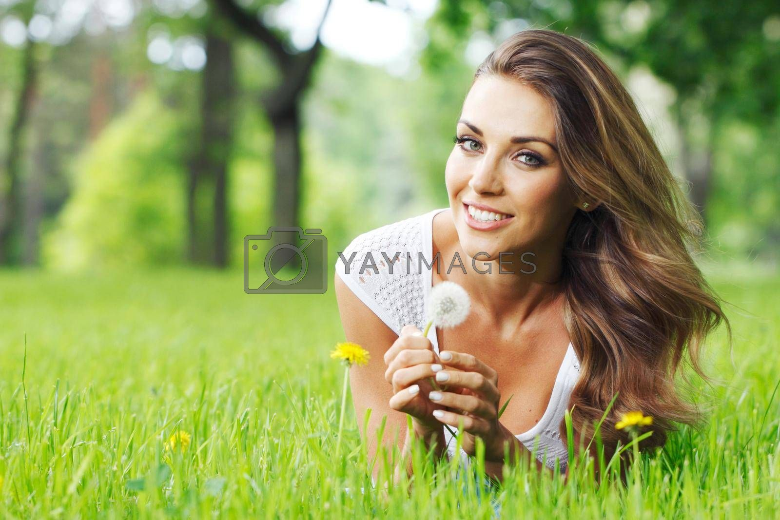 Royalty free image of Woman lay in park with dandelion by Yellowj
