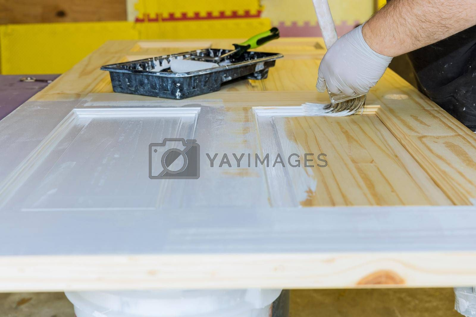 Handyman home renovation painter of painting doors trim using hand paint brush painting with gloves