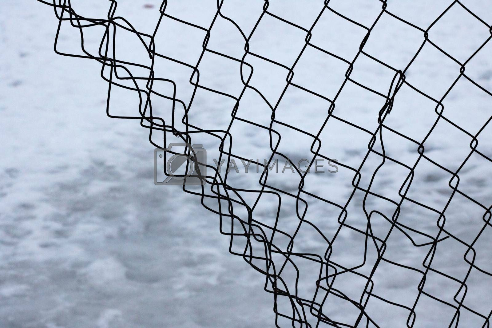 Torn mesh fence on a snow background close up, copy space